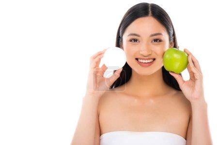 Photo pour Brunette asiatique femme tenant fraîche pomme verte et crème cosmétique tout en regardant caméra isolé sur blanc - image libre de droit