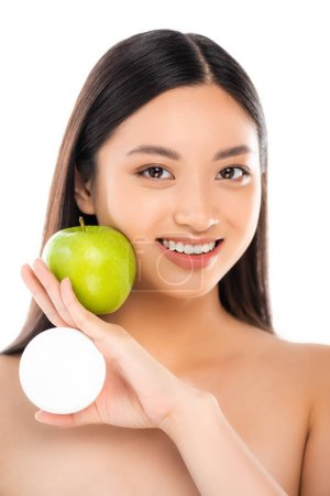 naked asian woman holding ripe green apple and cosmetic cream near face isolated on white