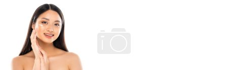 Photo for Horizontal crop of young asian woman looking at camera while applying cosmetic cream on face isolated on white - Royalty Free Image