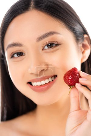 Photo for Selective focus of asian woman holding ripe strawberry near face isolated on white - Royalty Free Image