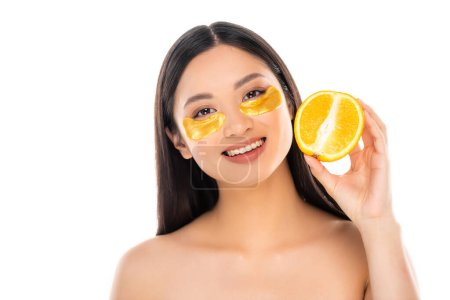 Photo pour Nude asian woman with golden eye patches on face holding half of juicy orange isolated on white - image libre de droit