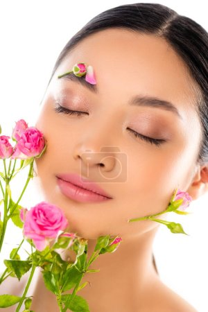 Photo pour Portrait of sensual asian woman with closed eyes, flowers on face, near tiny roses isolated on white - image libre de droit