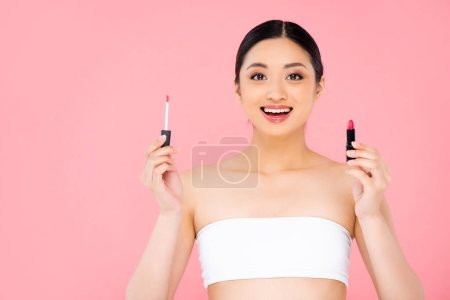 Photo for Excited asian woman holding lip gloss and lipstick while looking at camera isolated on pink - Royalty Free Image