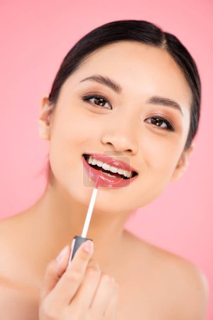 brunette asian woman looking at camera while applying lip gloss isolated on pink