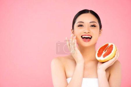 Photo for Excited asian woman holding half of juicy grapefruit while touching face isolated on pink - Royalty Free Image