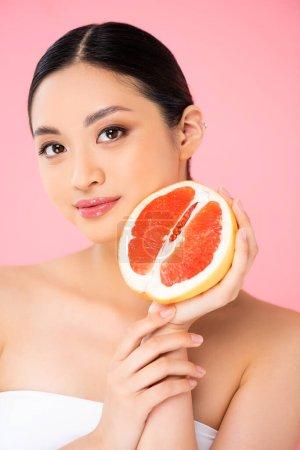 joven asiático mujer sosteniendo la mitad de maduro pomelo mientras mirando a cámara aislado en rosa