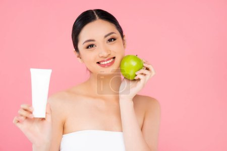 Photo for Young asian woman holding cosmetic cream and ripe green apple isolated on pink - Royalty Free Image