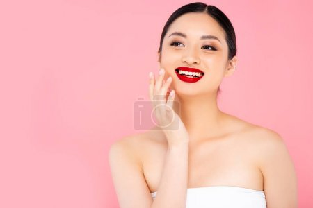 Photo pour Young asian woman with red lipstick on lips touching face while looking away isolated on pink - image libre de droit