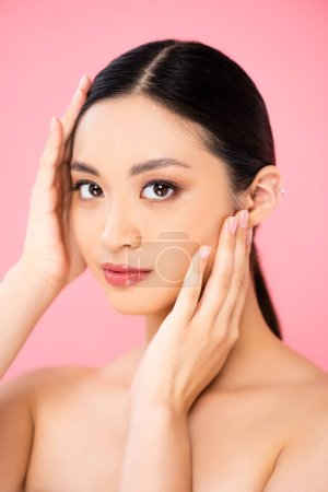 naked asian woman touching face while looking at camera isolated on pink
