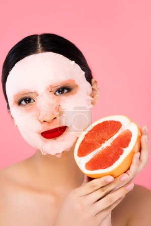 Photo for Young asian woman in face mask holding half of fresh grapefruit while looking at camera isolated on pink - Royalty Free Image