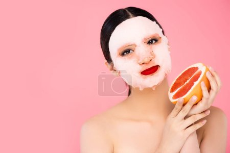 morena asiática mujer en la cara máscara celebración de la mitad de maduro pomelo mientras mira la cámara aislado en rosa