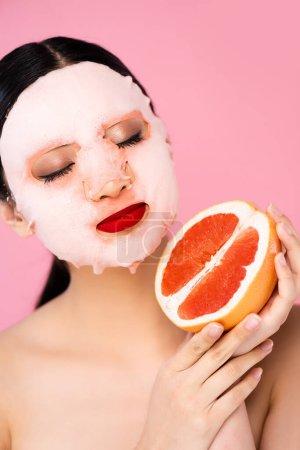 morena asiática mujer en la cara máscara celebración de la mitad de maduro pomelo con los ojos cerrados aislado en rosa