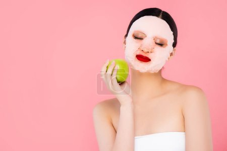 Photo for Young asian woman in face mask holding green apple with closed eyes isolated on pink - Royalty Free Image