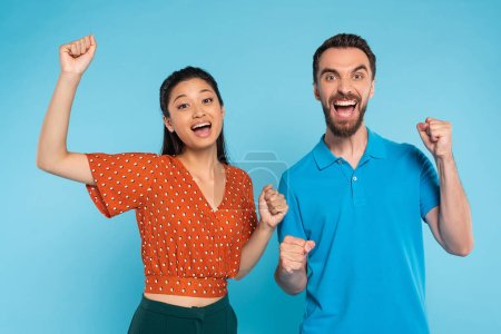 Photo pour Excited interracial couple looking at camera while showing triumph gesture on blue - image libre de droit