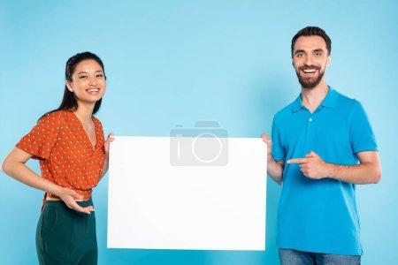 homme barbu en polo t-shirt et femme asiatique en chemisier pointillé rouge tenant la pancarte vierge sur bleu