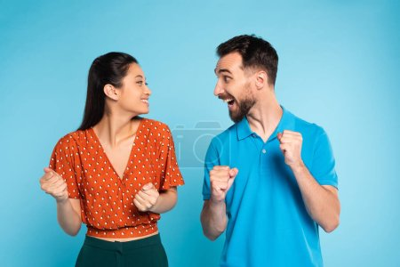 Photo pour Excited man in polo t-shirt and asian woman in red blouse looking at each other while showing win gesture on blue - image libre de droit