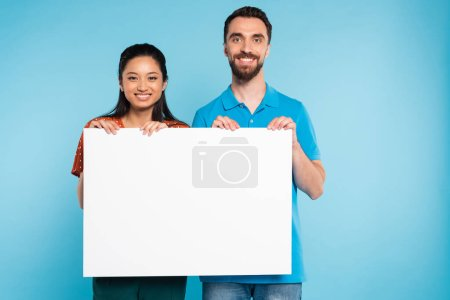 Photo for Young interracial couple looking at camera while holding empty board on blue - Royalty Free Image