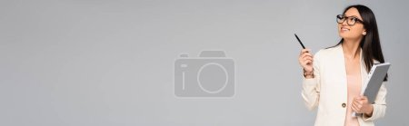 Photo for Horizontal image of asian businesswoman in eyeglasses looking away and pointing with pen isolated on grey - Royalty Free Image