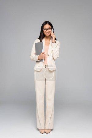 volle Länge Ansicht der stilvollen asiatischen Geschäftsfrau, die auf dem Smartphone spricht, während sie Ordner mit Dokumenten auf grau hält