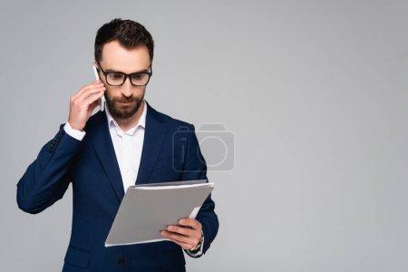 hombre de negocios serio en blazer azul y anteojos mirando los documentos mientras habla en el teléfono inteligente aislado en gris