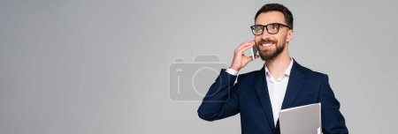 Photo pour Panoramic concept of businessman in eyeglasses and blue blazer talking on mobile phone isolated on grey - image libre de droit