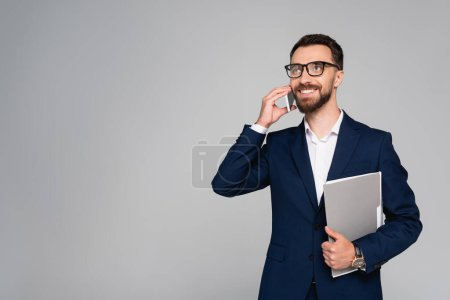 Photo pour Bearded businessman in blue blazer and eyeglasses looking away while talking on smartphone isolated on grey - image libre de droit