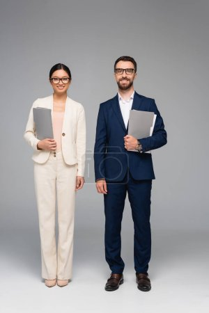 Photo for Interracial couple of business partners in suits holding folders and looking at camera on grey - Royalty Free Image