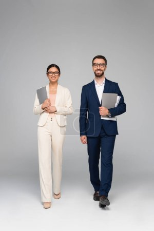 interracial couple of business colleagues looking at camera while walking with folders on grey