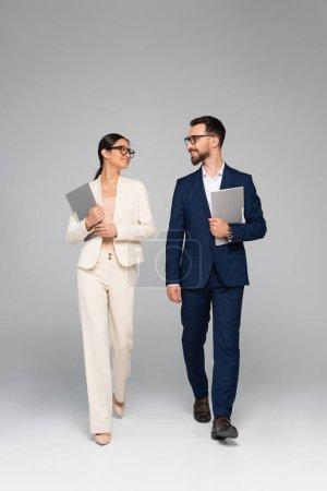 Photo pour Couple interracial de partenaires commerciaux tenant des dossiers et se regardant tout en marchant sur gris - image libre de droit