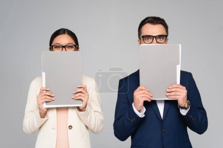 Photo pour Interracial couple of businesspeople in eyeglasses obscuring faces with folders isolated on grey - image libre de droit