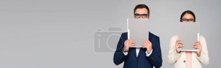 Photo for Panoramic concept of interracial couple of businesspeople obscuring faces with folders isolated on grey - Royalty Free Image