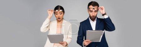 Photo pour En-tête du site de surpris couple interracial de collègues d'affaires touchant lunettes tout en regardant les dossiers isolés sur gris - image libre de droit