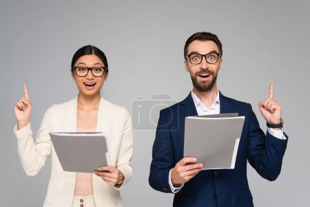 excited couple of interracial business colleagues showing idea gesture while holding folders isolated on grey