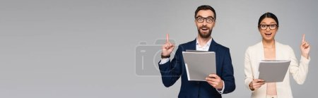 Photo pour Panoramic shot of excited couple of interracial businesspeople showing idea sign while holding folders isolated on grey - image libre de droit