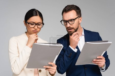 Photo pour Thoughtful interracial business partners in eyeglasses touching chins while looking at documents isolated on grey - image libre de droit