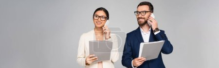 Photo for Panoramic concept of interracial businesspeople talking on mobile phones while holding folders isolated on grey - Royalty Free Image