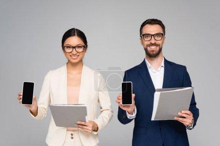 Photo pour Couple de collègues d'affaires interracial tenant des dossiers et des smartphones avec écran blanc isolé sur gris - image libre de droit