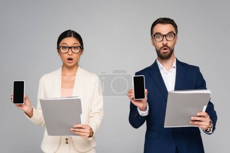 Photo pour Shocked interracial business partners holding folders while showing mobile phones with blank screen isolated on grey - image libre de droit