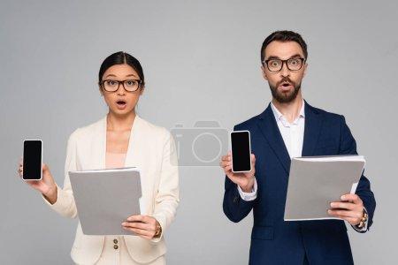 Photo pour Choqué partenaires d'affaires interracial tenant des dossiers tout en montrant les téléphones mobiles avec écran blanc isolé sur gris - image libre de droit