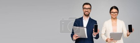 Photo for Horizontal image of interracial couple of businesspeople showing smartphones with blank screen while holding folders isolated on grey - Royalty Free Image