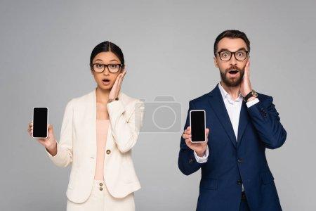 Photo pour Surpris couple interracial de collègues d'affaires toucher les visages tout en tenant les smartphones avec écran blanc isolé sur gris - image libre de droit