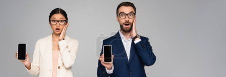 Photo for Shocked interracial businesspeople touching faces while showing smartphones with blank screen isolated on grey, horizontal concept - Royalty Free Image