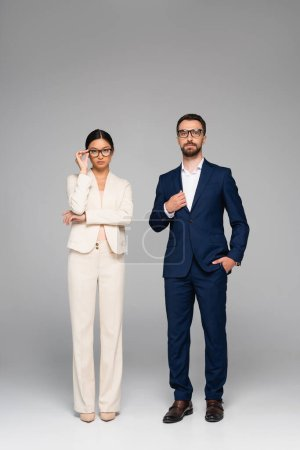 Photo for Couple of confident interracial business partners looking at camera while standing on grey - Royalty Free Image