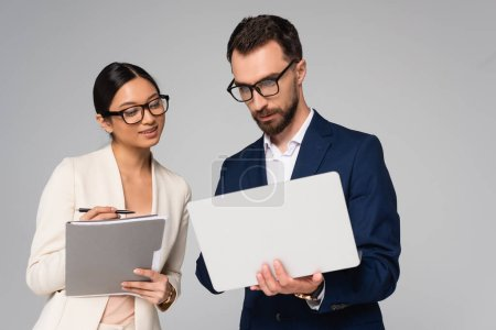 couple of interracial businesspeople in eyeglasses with laptop and folder isolated on grey