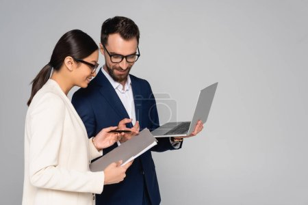 bearded businessman pointing with finger at folder in hands of asian colleague while holding laptop isolated on grey