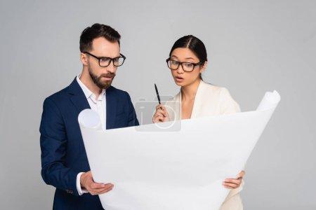 Photo pour Couple interracial réfléchi de partenaires d'affaires dans des lunettes de vue regardant plaque blanche isolée sur gris - image libre de droit