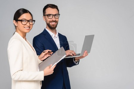 Photo pour Asian businesswoman with folder and businessman with laptop looking at camera isolated on grey - image libre de droit