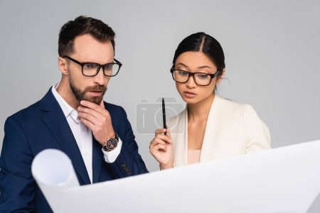 Photo for Thoughtful interracial couple of business colleagues in eyeglasses looking at white paper isolated on grey - Royalty Free Image