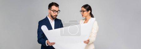 Photo pour Image horizontale d'un couple interracial d'hommes d'affaires tenant une pancarte isolée sur du gris - image libre de droit