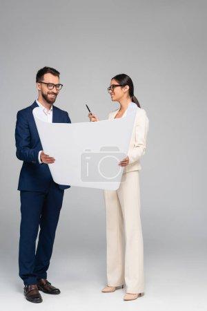 Photo pour Asian businesswoman talking to business partner while holding white paper on grey - image libre de droit